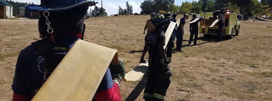 Firefighters loading hose